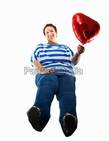 large woman carrying heart balloon