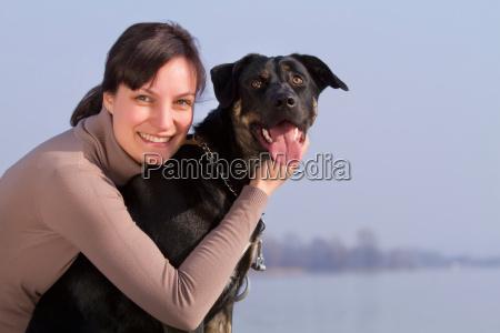 woman hugging dog outdoors