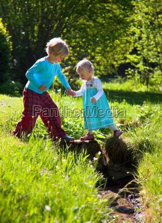 boy helping sister cross creek
