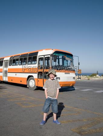 boy standing near public bus