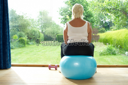 woman sitting on exercise ball indoors