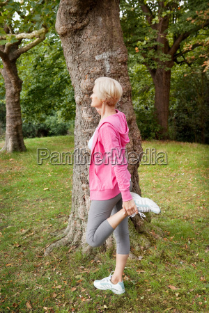 mature woman stretching leg in park