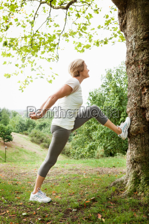 mature woman stretching in park