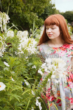 woman looking at flowers in park