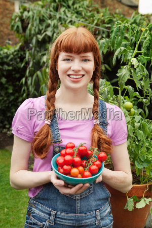 woman holding bowl with picked tomatoes