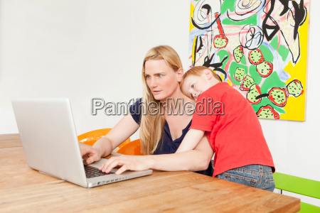 mother and son using laptop together