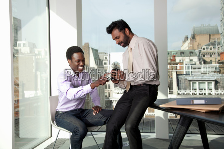 two men discussing mobile telephone