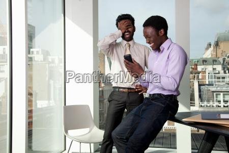 two men laughing at telephone display