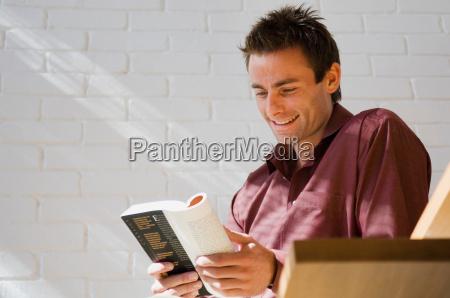 smiling man reading book