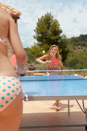 girls playing table tennis outdoors