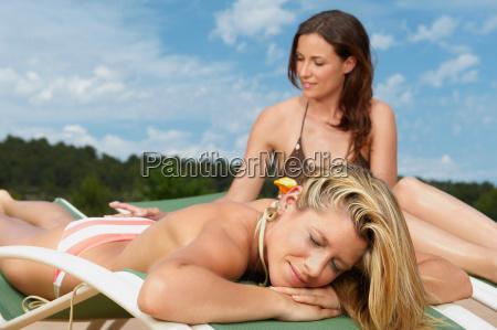 woman applying sunblock on female friend