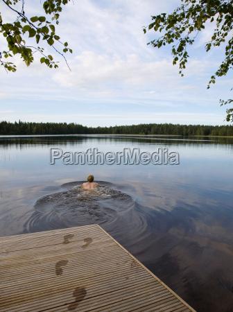 man swimming in still lake