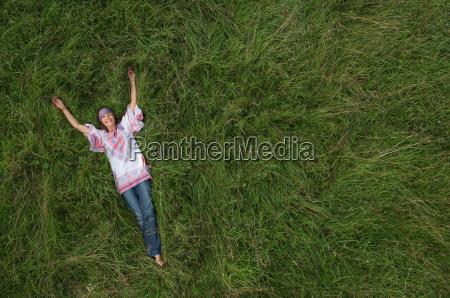 hippy female relaxing in field