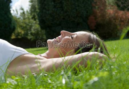 female lying on grass smiling