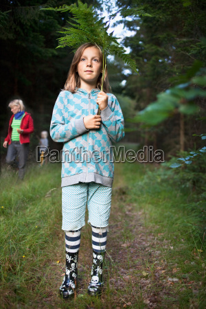 girl wearing rain boots in forest