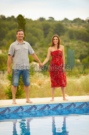 couple, holding, hands, by, swimming, pool - 18446398