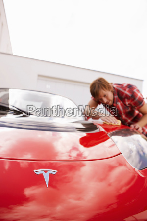 man proudly polishing hi electric car