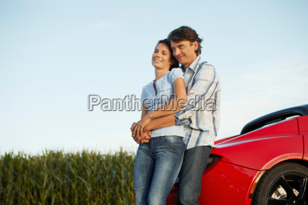 couple standing by their electric car