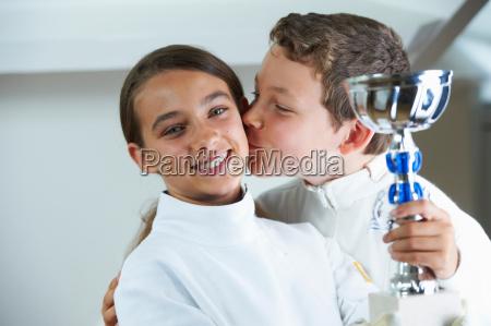 boy kissing smiling fencing rival