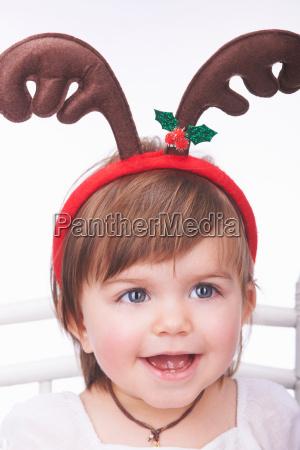 baby girl wearing reindeer antlers