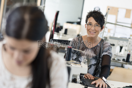 portrait of mature seamstress using sewing