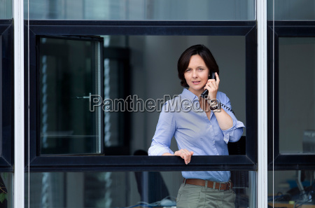 businesswoman looking out office window