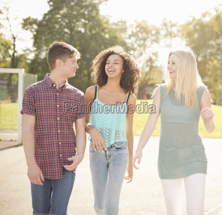 three young adult friends strolling in