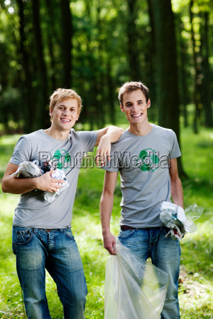 two young men collecting trash in