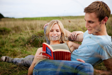 young couple laying together in nature