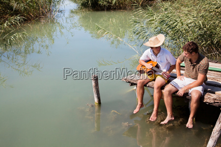 two men sit chatting on lake