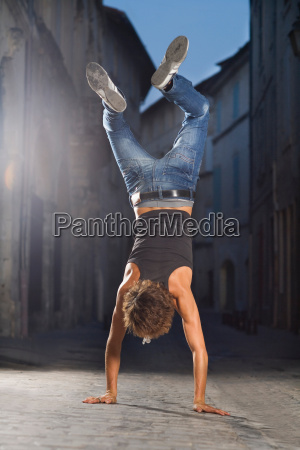 young man walks on hands in