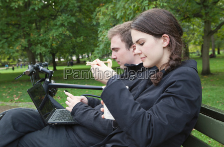woman eating noodles on park bench