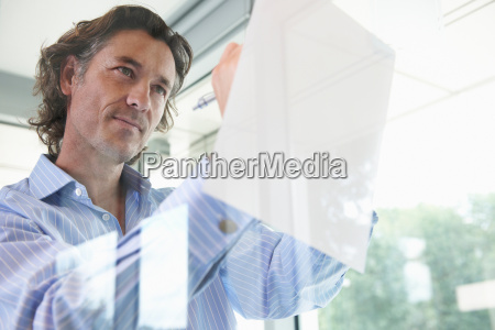 confident man writing leaning on window