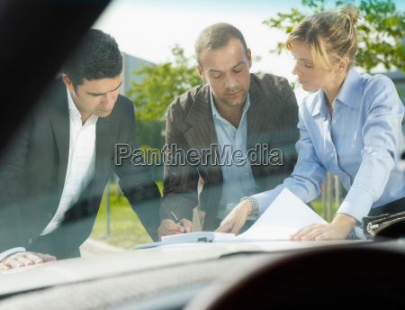 businesspeople signing contract on car