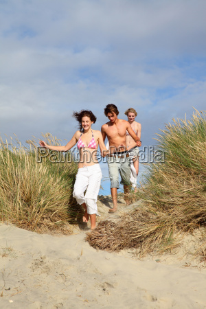 young friends running over dunes
