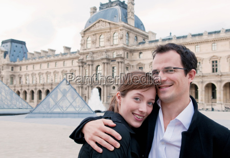 happy couple embrace outside the louvre