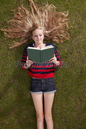 girl lying reading a book