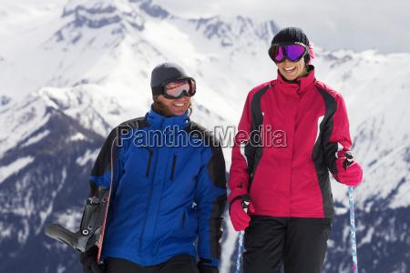 couple with ski poles on mountain