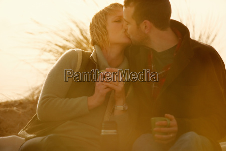 couple outdoors kissing with coffee