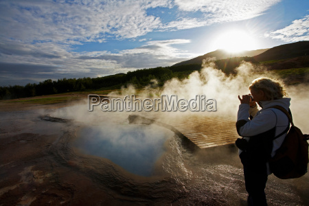 woman taking picture of geothermal river