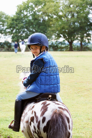 young girl riding her pony