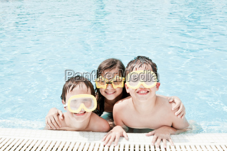 children in pool wearing swimming goggle
