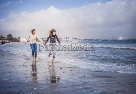 two young women friends running hand