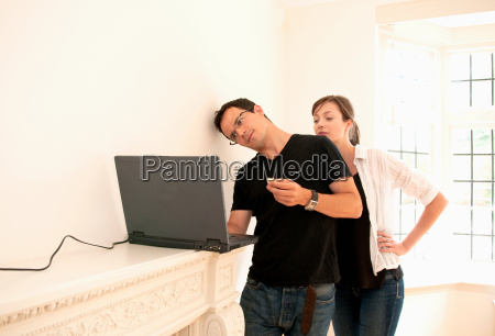 couple check emails in new home