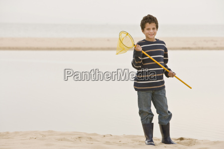 young boy at beach holding fishing