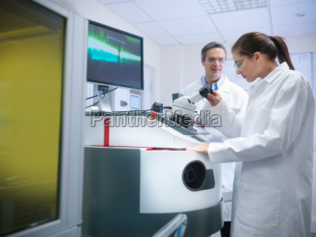 male and female scientists at laser