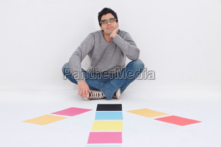 man sitting with coloured paper smiling