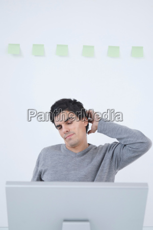man stretching at computer