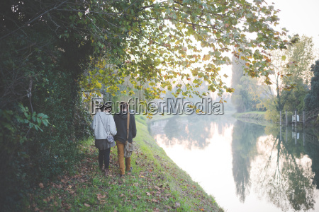 young couple walking by riverbank dolo
