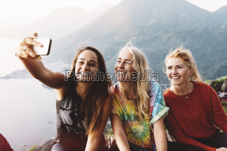 three female friends taking smartphone selfie
